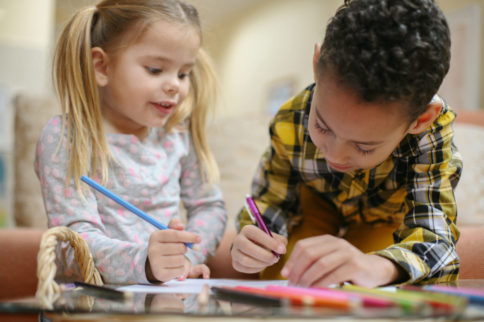 African American boy and Caucasian girl drawing together.