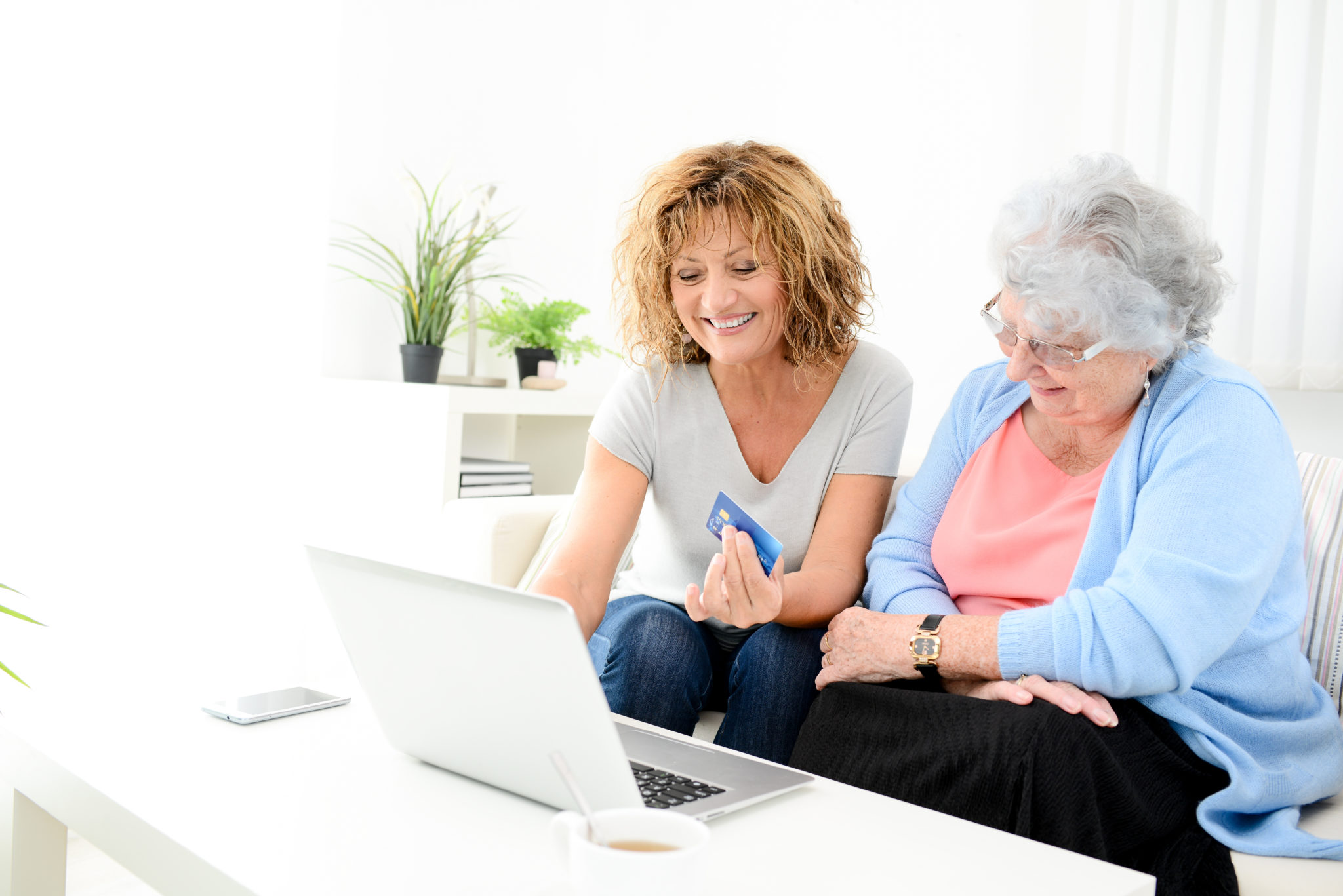 mature woman helping at home assisted elderly senior female buying and shopping online on internet with a laptop computer and credit card